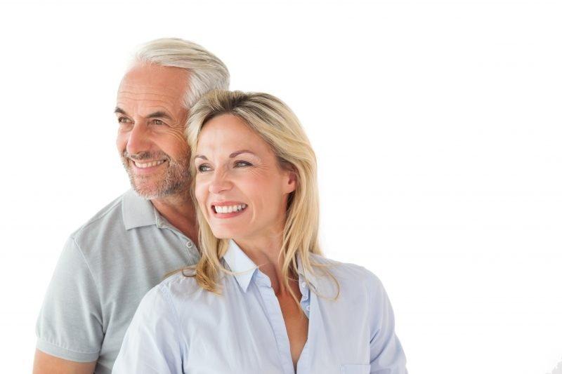 casal sênior sorrindo e exibindo implante dentário